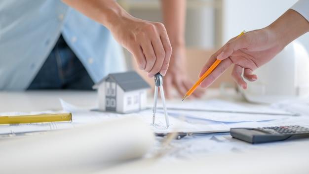 Foto de close-up de designers usando o equipamento para desenhar desenhos de casas.
