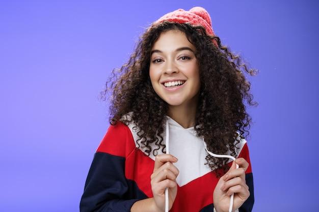 Foto de close-up de despreocupada garota feminina atraente com cabelo encaracolado em gorro brincando com moletom como posando sobre fundo azul, sorrindo para a câmera, se divertindo e uma atitude positiva.