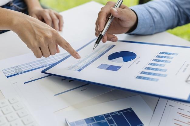 Foto de close-up de dois empresários apontando para uma folha de dados de vendas em formato de gráfico, eles se encontrando para discutir o tópico de gerenciamento do crescimento das vendas. conceito de cooperação empresarial e gestão de vendas.