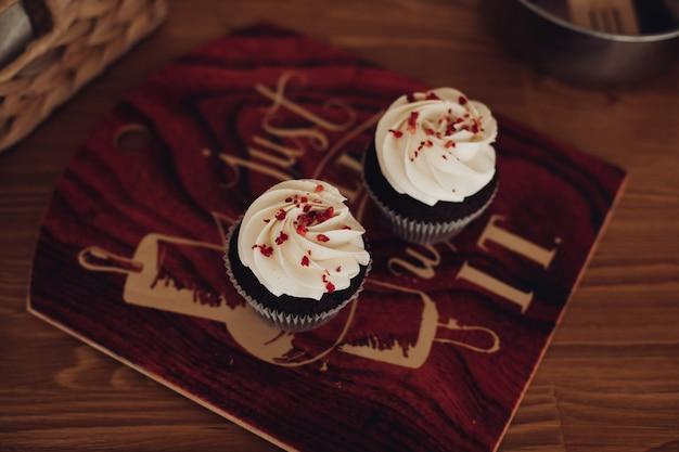 Foto de close-up de dois muffins caseiros pretos com muito creme branco sobre eles
