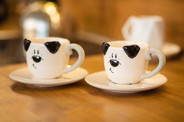 Foto de close-up de duas xícaras preto e branco com foto de cachorro na mesa marrom