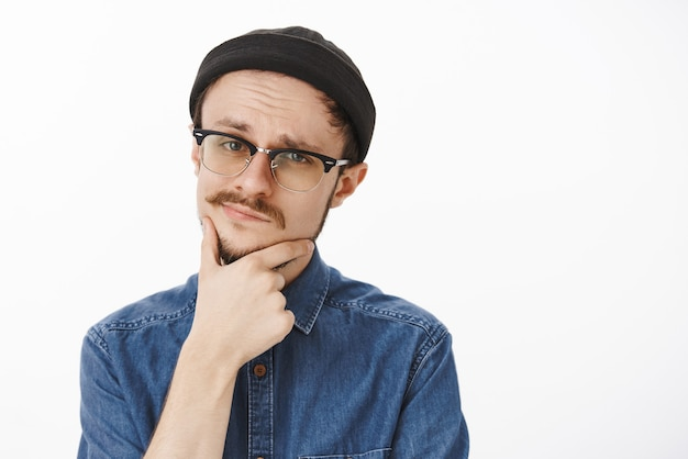 Foto de close-up de duvidoso inteligente suspeito jovem bonito com barba e bigode com gorro preto e óculos tocando o queixo e sorrindo torto, sentindo-se incerto e impressionado