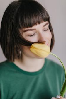 Foto de close-up de elegante garota europeia, apreciando o sabor de tulipa com os olhos fechados. retrato de jovem com cabelo curto, segurando uma flor amarela perto do rosto.