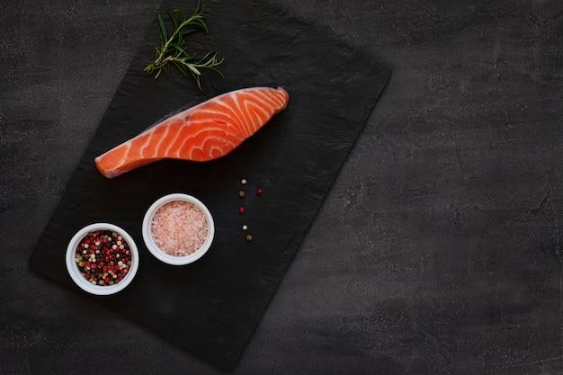Foto de close-up de filé de peixe salmão cru fresco com sal do mar, papel