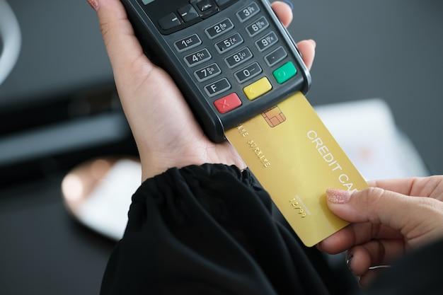 Foto de close-up de funcionários aceitando pagamentos com cartão de crédito via edc. pagamento e compras online.