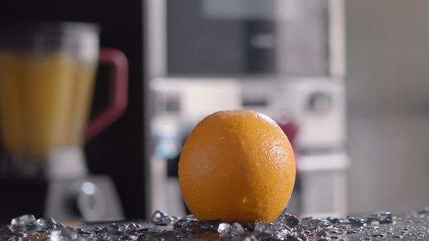 Foto de close-up de gelo caindo na laranja, liquidificador com suco em primeiro plano. bebidas de laranja frescas e saudáveis