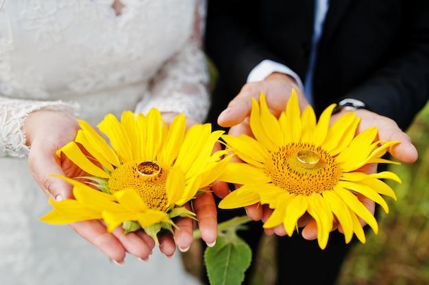 Foto de close-up de girassóis nas mãos do casal de noivos.