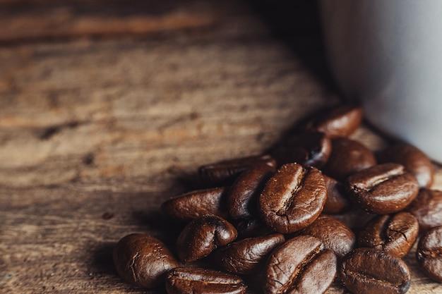 Foto de close-up de grãos de café na madeira.