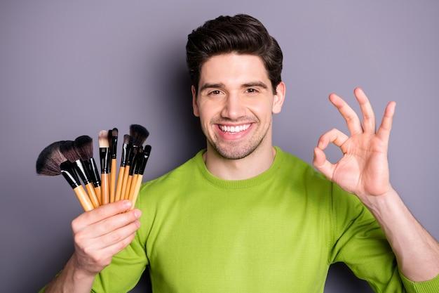 Foto de close-up de homem confiante e legal, trabalhador visagista, segurar borlas, escovas, mostrar sinal de bom, sugerir ótima festa, maquiagem, maquiagem, vestir, camisola verde