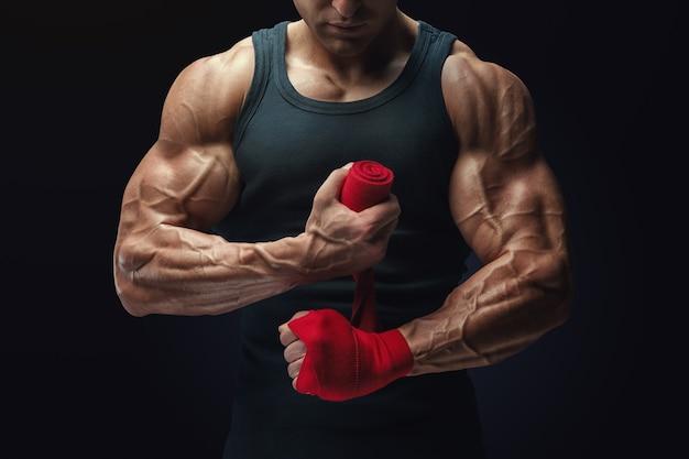 Foto de close-up de homem forte envolvendo mãos em fundo preto homem está envolvendo mãos com envoltórios de boxe vermelho isoladas em fundo preto mãos e punhos fortes, prontos para treinamento e exercícios ativos