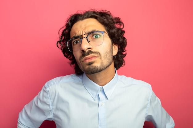 Foto de close-up de jovem bonito impressionado de óculos, olhando para a frente, isolada na parede rosa