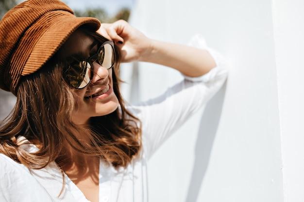 Foto de close-up de jovem em óculos de sol, posando na rua. mulher de boné marrom com sorriso encostado na parede.