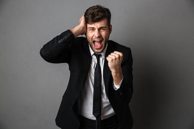 Foto de close-up de jovem gritando com raiva de terno preto, cobrindo a orelha e o punho cerrado