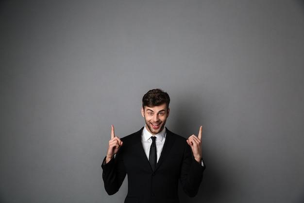 Foto de close-up de jovem sorridente com roupa formal, apontando com dois dedos para cima