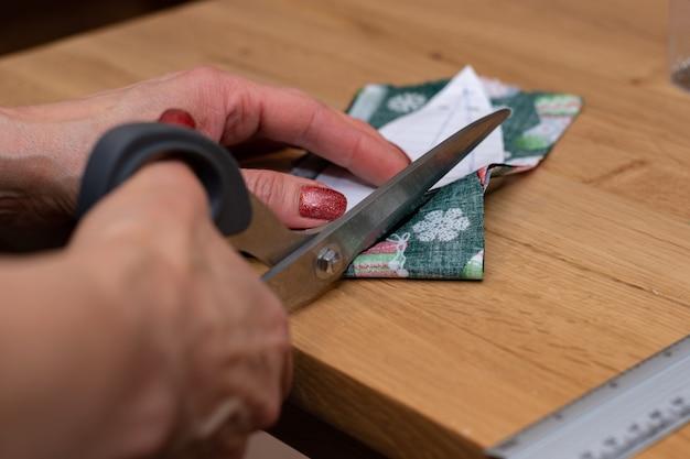 Foto de close-up de mãos da mulher corta tecido vermelho com tesoura e fazendo decorações.