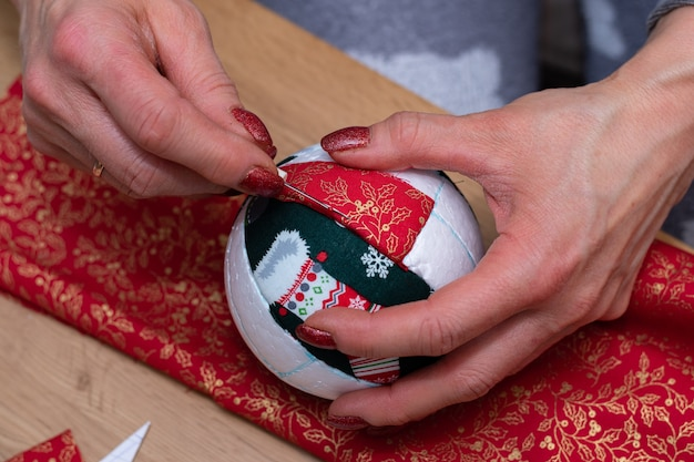 Foto de close-up de mãos de mulher corta tecido vermelho com tesoura e fazendo decorações.