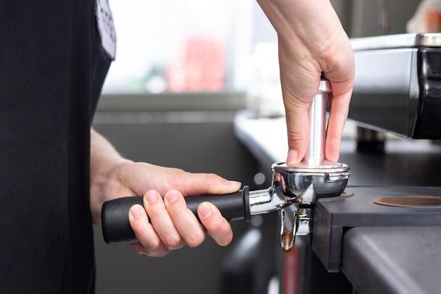 Foto de close-up de mãos femininas segurando um adulterador de metal e um porta-filtro com café em uma cafeteria