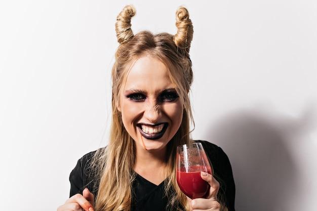 Foto de close-up de menina alegre bebendo sangue no dia das bruxas. vampiro despreocupado com cabelo loiro, posando no carnaval.
