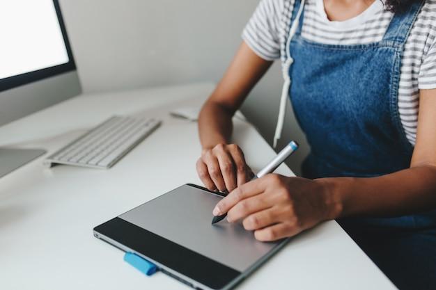 Foto de close-up de menina com pele castanha clara trabalhando com um novo dispositivo enquanto está sentada no escritório