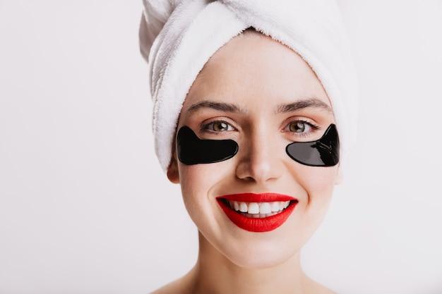 Foto de close-up de menina de olhos verdes com adesivos hidratantes. jovem mulher com lábios vermelhos, sorrindo sobre uma parede branca.