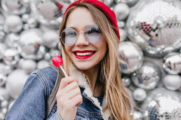 Foto de close-up de menina sorridente em jaqueta jeans, posando com pirulito vermelho. retrato do incrível modelo feminino branco em pé perto de bolas de discoteca com doces.