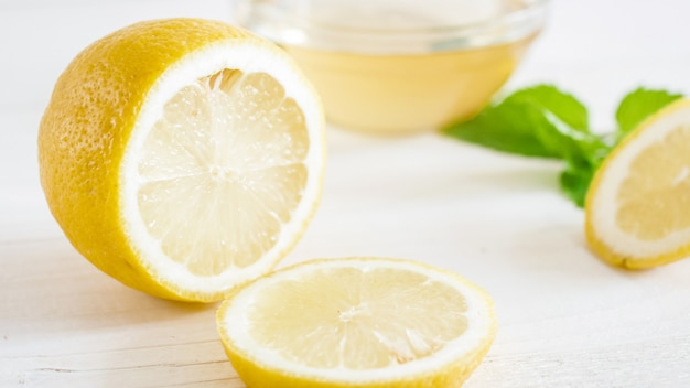 Foto de close-up de metade de limão e fatias deitado sobre placas de madeira brancas.