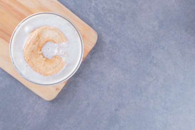 Foto de close-up de milk-shake de caramelo feito na hora na placa de madeira