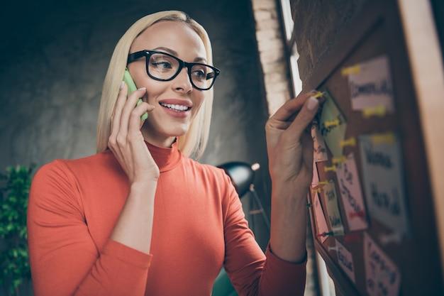 Foto de close-up de mulher alegre e positiva em gola alta vermelha, falar ao telefone com toque de parceiro, desenho de alfinete em notas de quadro de cortiça na estação de trabalho do loft do escritório