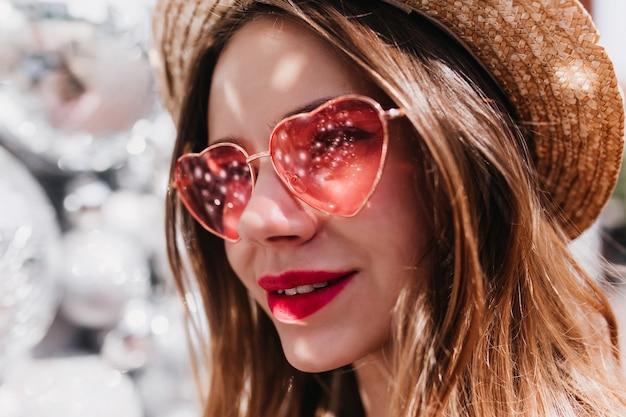 Foto de close-up de mulher atraente pensativa com chapéu de palha. debonair caucasiana garota em elegantes óculos de sol rosa, olhando para longe.