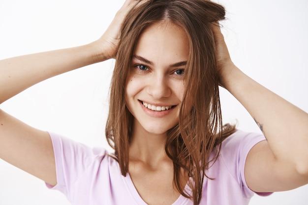 Foto de close-up de mulher bonita, confiante e feminina, tocando o corte de cabelo e sorrindo alegremente, sentindo-se bem para se livrar da acne sobre a parede cinza