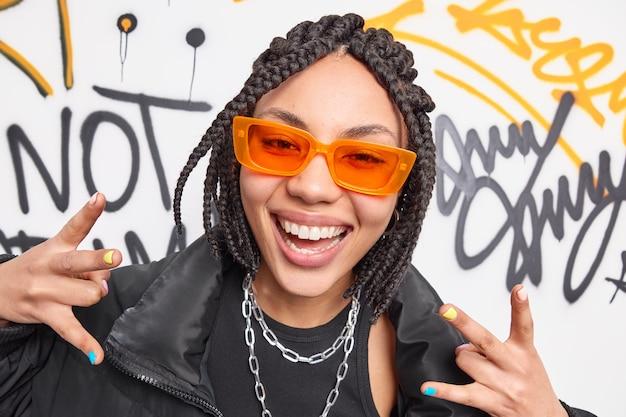 Foto de close-up de mulher com sorriso positivo, sentindo gestos legais usando óculos de sol laranja, correntes de metal no pescoço, jaqueta preta posa contra parede de grafite
