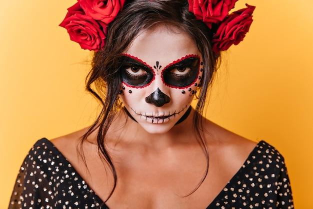 Foto de close-up de mulher de olhos castanhos com arte de rosto de carnaval. modelo mexicano está com raiva, olhando para a câmera em fundo laranja.