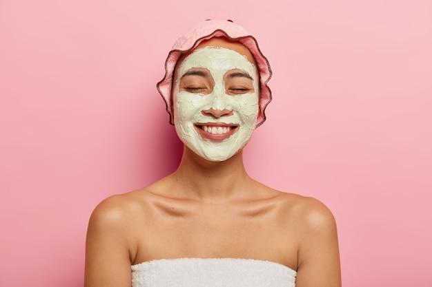 Foto de close-up de mulher japonesa encantada aplicando máscara cosmética, quer ter pele fresca, recriação em resort spa, mostra ombros nus, usa touca de banho, tem sorriso largo, isolado na parede rosa