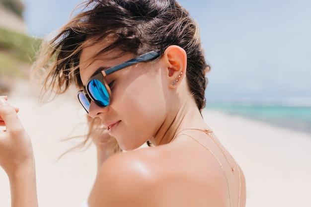 Foto de close-up de mulher jovem de cabelos escuros sensual em óculos de sol brilhantes. linda mulher relaxada em pé na praia na manhã quente.