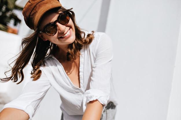 Foto de close-up de mulher posando na rua. garota com roupa elegante de verão e cocar está sorrindo contra o espaço do farol.