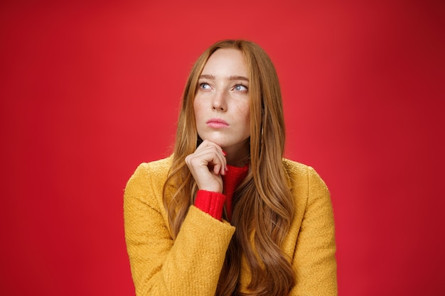 Foto de close-up de mulher ruiva pensativa criativa determinada e focada olhando para o canto superior esquerdo tocando o queixo, pensando, fazendo escolhas ou lembrando informações sobre fundo vermelho.