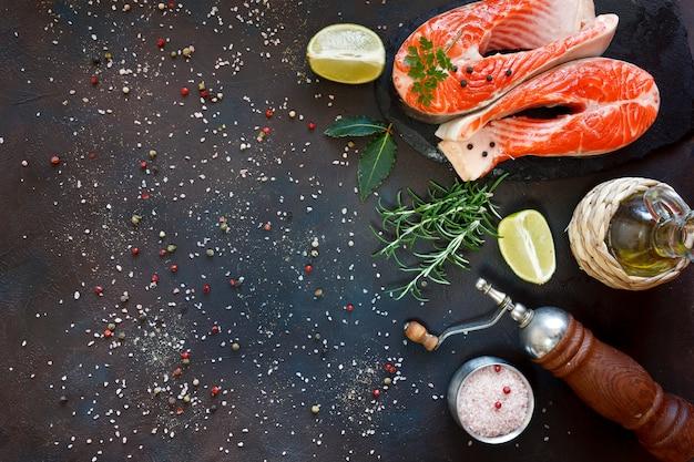 Foto de close-up de peixe salmão fresco com sal do mar e fatias de limão na mesa preta