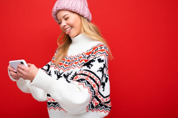Foto de close-up de perfil lateral de uma bela jovem loira sorridente usando um chapéu de malha quente e