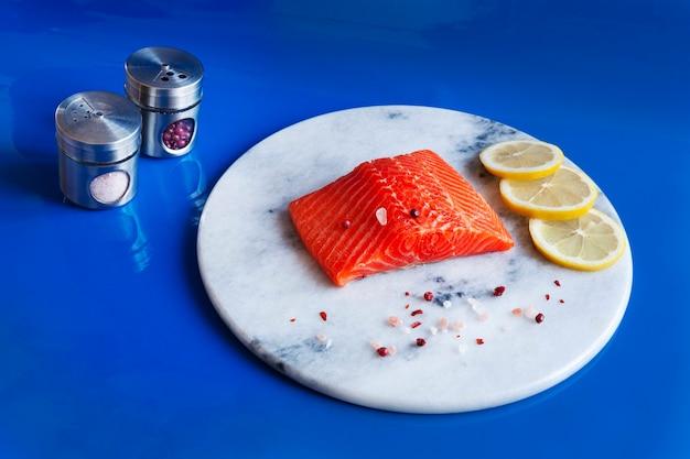 Foto de close-up de salmão cru fresco, filé de truta na tábua de mármore com sal, pimenta e rodelas de limão