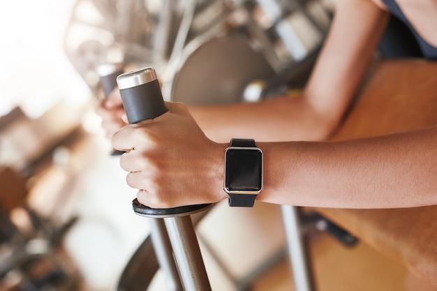 Foto de close up de tecnologias inteligentes de relógio inteligente preto na mão de uma mulher malhando