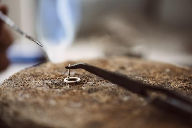 Foto de close up de trabalho delicado de mãos de joalheiro soldando um brinco de prata com uma chama de