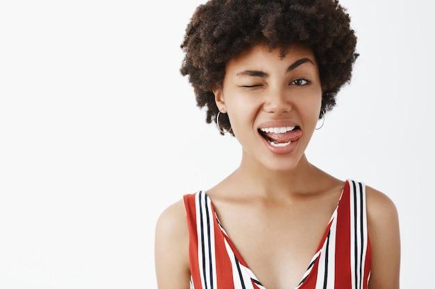 Foto de close-up de um afro-americano atraente, emotivo e brincalhão com penteado afro mostrando a língua e piscando