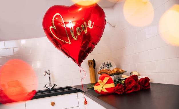 Foto de close-up de um buquê de rosas vermelhas, um grande balão e uma caixa vermelha em forma de coração com uma fita dourada, que estão sobre uma mesa da cozinha.