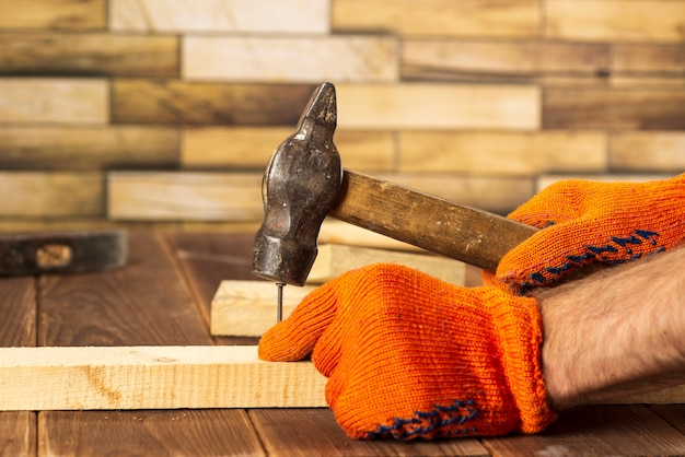 Foto de close-up de um carpinteiro com luvas laranja martela um prego em uma placa de madeira