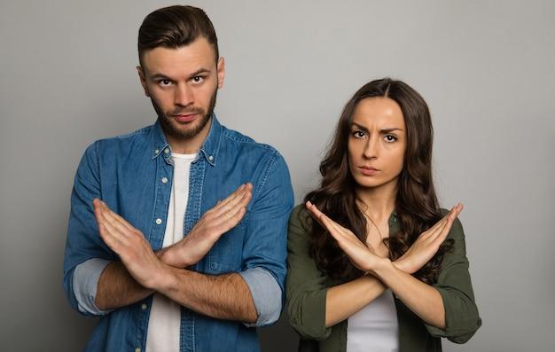 Foto de close-up de um casal sério em trajes casuais, olhando para a câmera com as mãos cruzadas em sinal de recusa.