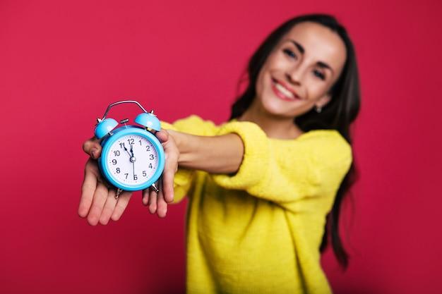 Foto de close-up de um despertador turquesa, segurado por uma mulher bonita e sorridente em um suéter amarelo quente