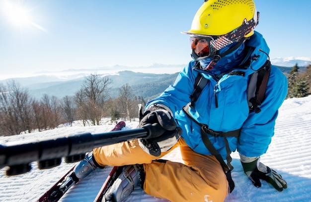 Foto de close-up de um esquiador deitado na neve no topo de uma encosta, tomando uma selfie usando a câmera no conceito de tecnologia monopé selfie stick de manhã.