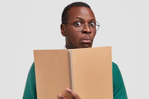 Foto de close-up de um estudante negro estupefato em uma aula, segurando um caderno espiral para anotar informações e usando óculos ópticos