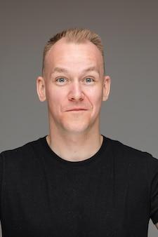 Foto de close-up de um homem amigável de camisa preta posando para foto de passaporte