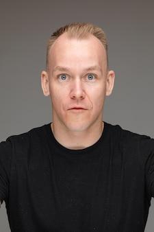 Foto de close-up de um homem branco surpreso de camisa preta